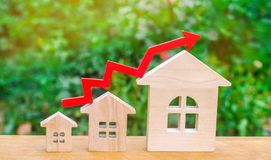 Wooden houses stand in a row from small to large with a red arrow up. concept of high demand for real estate. increase energy effi. Ciency of housing. rise in Stock Photos