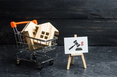 Wooden houses in a supermarket cart and up arrow. uction for the purchase of housing and buildings. The growth of the city stock photos