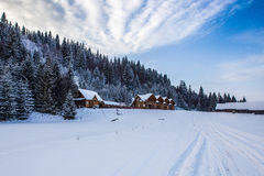 Wooden houses in winter snowy forest Royalty Free Stock Image