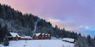Wooden houses in winter snowy forest. From top of hill stock image