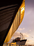Wooden hull of boat at sunset in drydock Royalty Free Stock Image