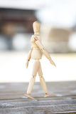 Wooden human. Wooden artist mannequin isolated on wooden table stock photo