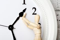 Wooden human figure trying to stop the arrow of the clock royalty free stock photos