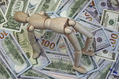 Wooden Human Figurine On The Dollar Cash Background Stock Image