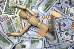Wooden Human Figurine On The Dollar Cash Background Stock Photo