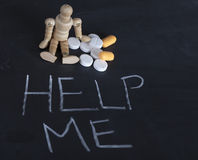 Wooden human figurine with pills and help me on chalkboard. Wooden human figure with pills and help me on chalkboard Royalty Free Stock Photography