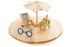 Wooden human model in relax time with blue bicycle in tray Royalty Free Stock Image