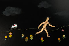 Wooden human model running with white dog paper cut in flower garden Stock Photography