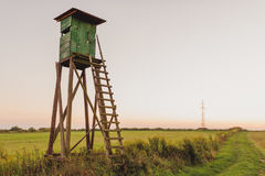 Wooden Hunting high tower. Hunters tower. Wooden Hunting high tower on the meadow. Hunters lookout tower royalty free stock photo