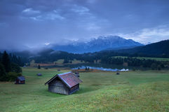 Wooden hut on alpine meadow by lake Stock Image