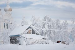 Snow hut. A wooden hut covered with snow stands among snowdrifts and trees on top of a mountain near the Russian monastery Stock Photo