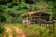 Wooden hut and fence. Rural landscape with road royalty free stock photography