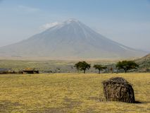Wooden hut in front of volcano. Africa stock photography