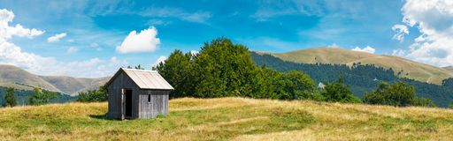 Wooden hut on a grassy meadow. Forested mountains in the distant. beautiful panorama of summer countryside Stock Photography
