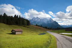 Wooden hut on meadow and high Bavarian alps Stock Photography