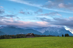 Wooden hut on meadow and sunset clouds over mountains Stock Images