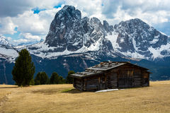Wooden hut on a mountain with the Dolomites on the background Royalty Free Stock Photo