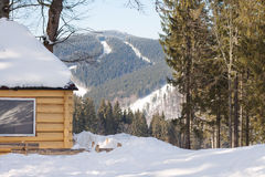 Wooden hut in a mountain forest in winter Stock Photos