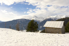 Wooden hut in mountain snow. Scenic landscape view of a traditional wooden hut in winter snow against a backdrop of snow-covered mountain peaks Stock Photo