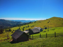 A wooden hut on mountains with green meadow Royalty Free Stock Photos