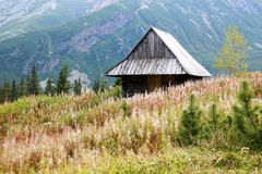 Wooden hut among the mountains stock photography