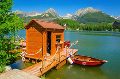 Wooden hut and red boats on lake Strbske pleso Stock Photography