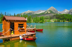Wooden hut and red boats on mountain lake Royalty Free Stock Image