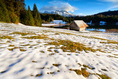 Wooden hut on smow alpine meadow by lake Royalty Free Stock Image