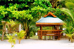 Wooden hut on the white coral sand beach surrounded with lush vegetation Stock Photo