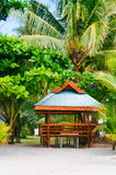Wooden hut on the white coral sand beach surrounded with lush vegetation Stock Photos