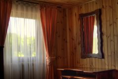 Wooden hut window. Window with curtains against a mirror in a wooden hut Royalty Free Stock Image