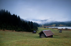 Wooden huts and fog over Geroldsee lake in dusk Royalty Free Stock Images