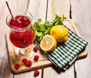 On wooden is ice cold beverage glass with raspberry cocktail . Stock Image