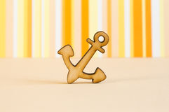 Wooden icon of anchor on orange striped background Royalty Free Stock Image
