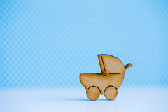 Wooden icon of baby buggy on blue background Royalty Free Stock Image