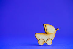 Wooden icon of baby buggy on blue background Stock Photos