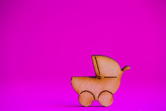 Wooden icon of baby buggy on crimson background Royalty Free Stock Image