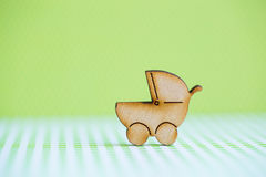 Wooden icon of baby buggy on green background Royalty Free Stock Photography