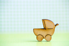 Wooden icon of baby buggy on green checkered background Stock Image