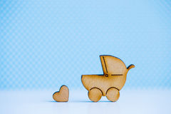 Wooden icon of baby buggy and little heart on blue background Royalty Free Stock Photo