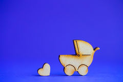 Wooden icon of baby buggy and little heart on blue background Stock Photo
