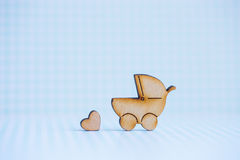 Wooden icon of baby buggy and little heart on blue checkered bac Royalty Free Stock Photos