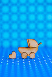 Wooden icon of baby buggy and little heart on blue spotted backg Stock Photos