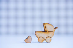 Wooden icon of baby buggy and little heart on checkered backgrou Stock Photography