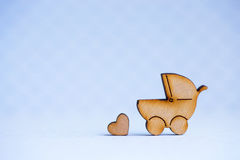 Wooden icon of baby buggy and little heart on gray background Royalty Free Stock Photo
