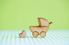 Wooden icon of baby buggy and little heart on green background Royalty Free Stock Image