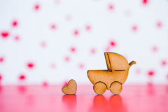 Wooden icon of baby buggy and little heart on pink and white bac Stock Photography