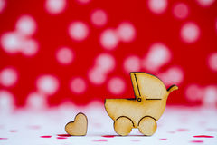 Wooden icon of baby buggy and little heart on red and white back Royalty Free Stock Photo