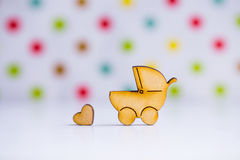 Wooden icon of baby buggy and little heart on spotted background Stock Photos