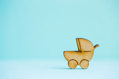Wooden icon of baby buggy on mint background Stock Image